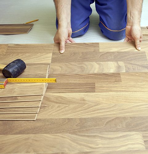 Carpenter installing wooden floor - home improvement